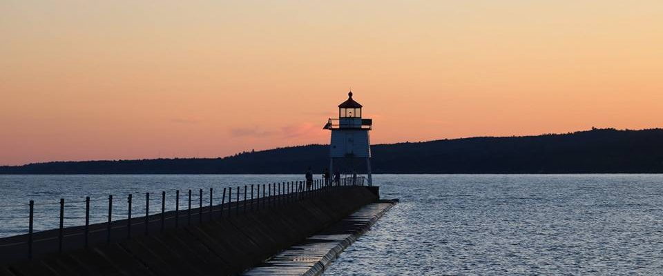 Lighthouse at the end of a pier surrounded by water against a red/pink evening sky